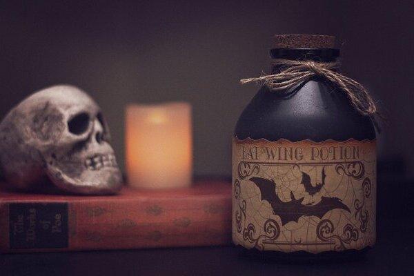 בקבוק עם שיקוי של צמחי מרפא מסוכנים ליד נר וגולגולת