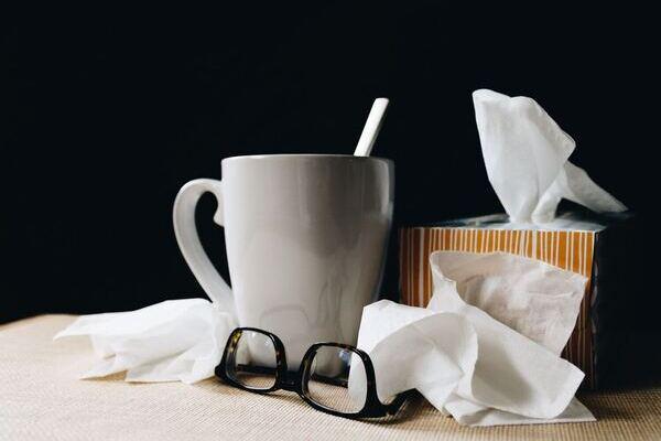 ממחטות טישו ליד כוס לבנה ומשקפיים